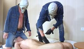Two masters in gas masks facesitting on a slave